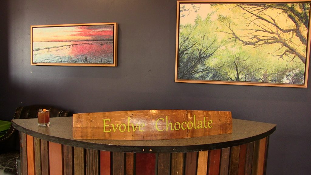 Evolve Chocolate table with paintings on wall behind